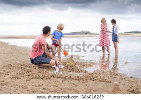 A family of four are playing on the beach together. They all look happy and are smiling. - stock photo
