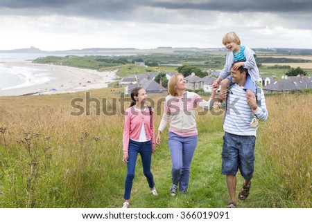A family of four are walking on the sand dunes together. The son is sitting on his fathers shoulders. They all look happy and are smiling. - stock photo