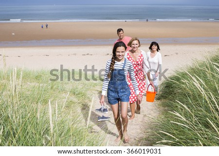 A family of four are walking up the sand dunes leaving the beach. They all look happy and are smiling. - stock photo