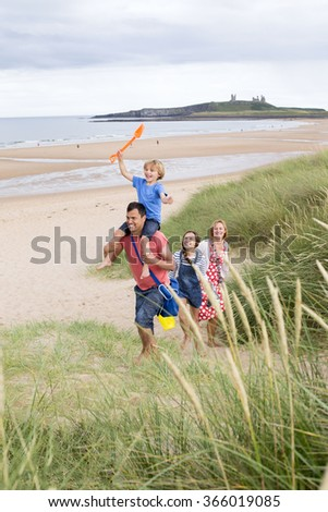 A family of four are walking up the sand dunes together, leaving the beach. The little boy is on his dads shoulders laughing. - stock photo