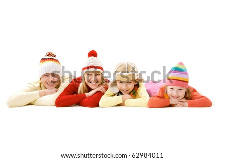 A family of four in warm clothes lying and smiling isolated on white - stock photo