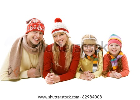 A family of four in warm clothing lying isolated on white - stock photo