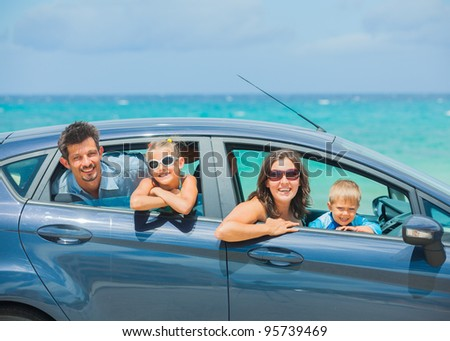 A family of four, mother, father, son and daughter driving in a car on a sunny day in hot location, backround sea - stock photo