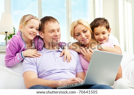 A family of four sitting on sofa and looking at laptop screen - stock photo