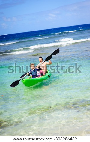 A family of three: father and his son and daughter having fun kayaking in the ocean - stock photo