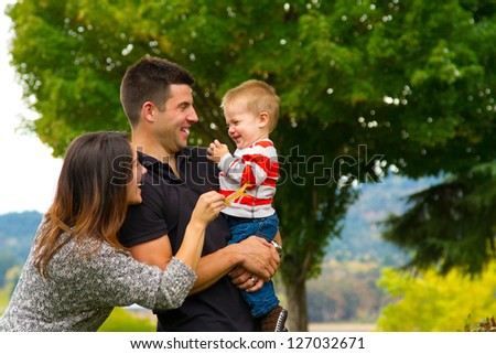 A family of three people play with leaves in the fall on a ranch.