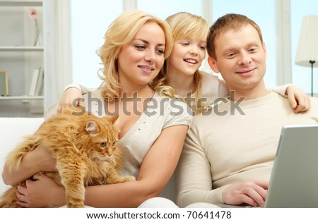 A family of three sitting on sofa and looking at laptop screen