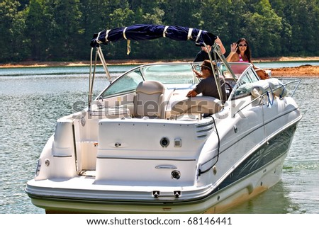 A family on a boat waving as they get ready to leave. - stock photo