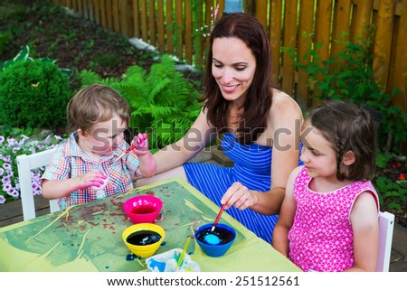 A family painting and decorating eggs.  A mother helps her children dye some eggs at a crafts table outside during Easter in the spring season in a beautiful garden setting.  Part of a series.    - stock photo