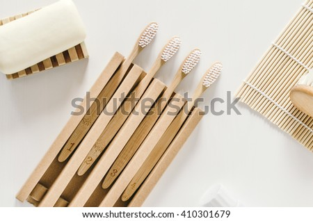 A family set of four wooden bamboo toothbrushes with bath other accessories  on white background - stock photo