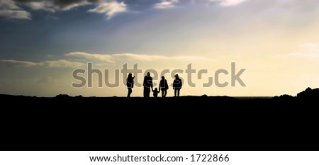A family silhouettes with a small child on sunset rays. - stock photo