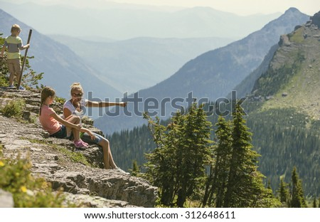 A family sitting together on a rocky ledge looking at a gorgeous view while visiting Glacier National Park in the Rocky Mountains - stock photo