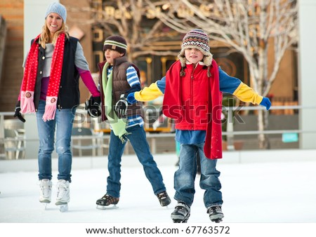 a family skates together at an ice rink - stock photo