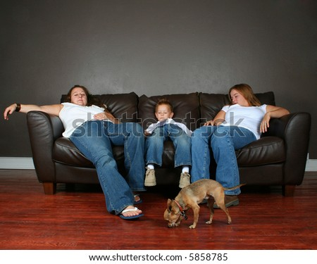 a family sleeping on a couch with a chihuahua
