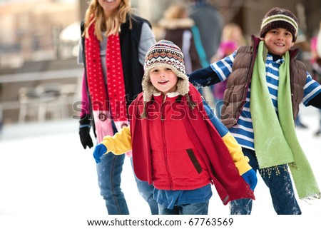 a family spends the day ice-skating outdoors - stock photo