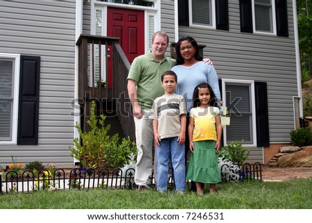 A family standing in front of their home - stock photo