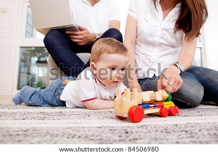 A family together in the living room, son playing on the floor - stock photo