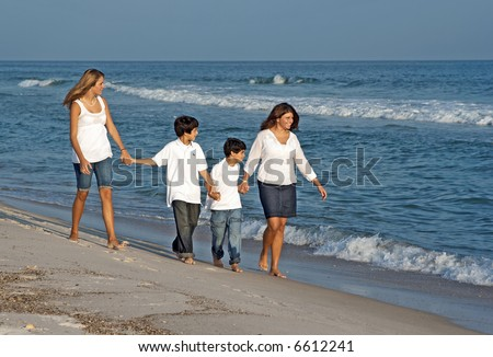 A family walking down the beach together. - stock photo