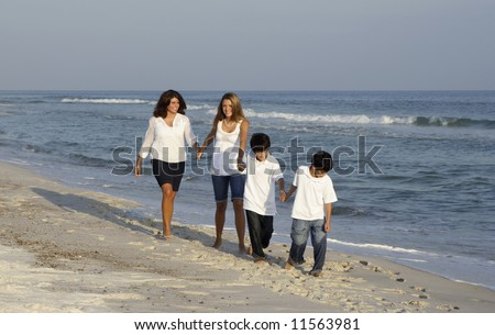 A family walking on the beach together. - stock photo