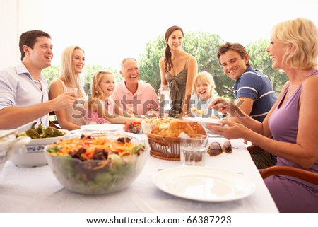 A family, with parents, children and grandparents, enjoy a picnic - stock photo