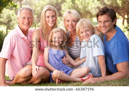 A family, with parents, children and grandparents, relaxing in a park - stock photo