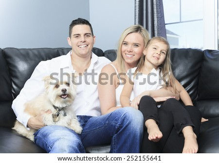 A Family with pets sit on sofa at home