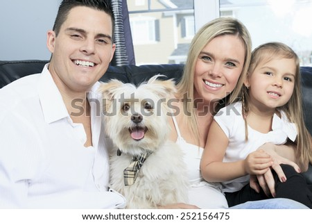 A Family with pets sit on sofa at home - stock photo