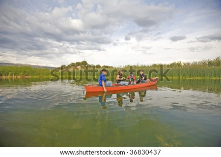 A family with their dog, fishing and spending time together in a canoe on a pond. - stock photo