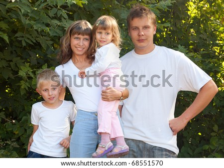 A family with two children at the background of green - stock photo