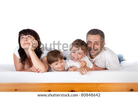 A family with two children on a bed in the bedroom - stock photo