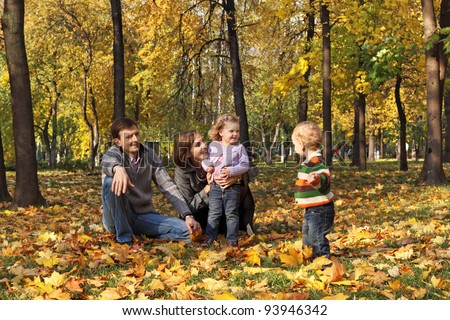 A family with two children walking in the autumn park among the fallen leaves - stock photo