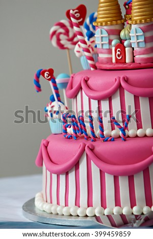 A fancy birthday cake with a candyland theme. The three layer cake is covered with fondant and candy decorations