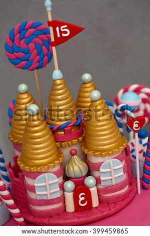 A fancy birthday cake with a candyland theme. The three layer cake is covered with fondant and candy decorations - stock photo