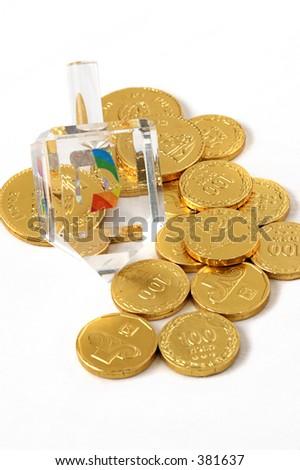 A fancy crystal Hanukkah dreidel and chocolate coins (gelt). Isolated. - stock photo