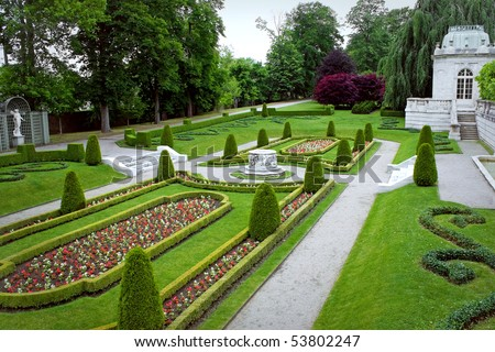 A fancy landscaped park or garden with flowers and highly groomed hedges. - stock photo