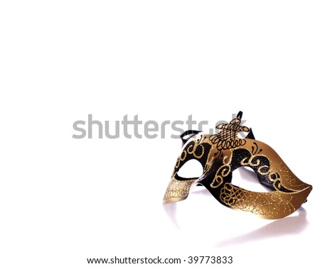 A fancy venetian mask shot against a white background with part of it's reflection in front - stock photo