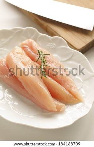 A fancy white plate with fresh pieces of fish near a wood cutting board. - stock photo