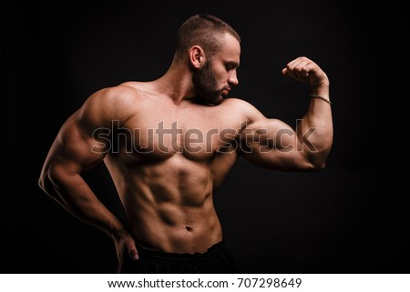 A fantastic macho man with muscular torso showing off his hand with perfect biceps and triceps after heavy exercises. A naked bodybuilder with strong abs working out hard on a black background.