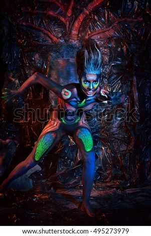 A fantastic scary zombie girl on the background of mystic scenery. Halloween. Studio high-resolution image.
