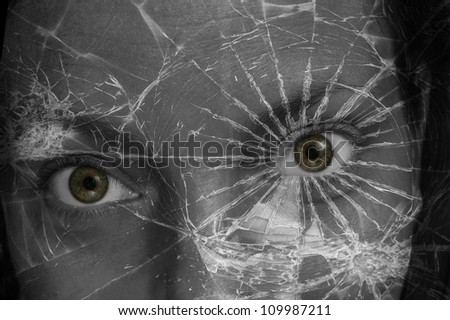 A fantastical photo of a green eyed woman peering through the shards of a broken pane of glass - stock photo
