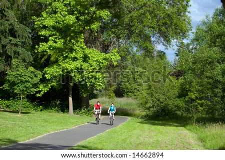 A far shot of a couple riding bicycles on a park trail together, smiling. - horizontally framed - stock photo