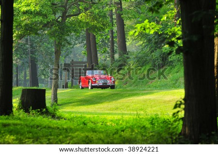 a far view of a red convertible classic sports car on the open country side road - stock photo