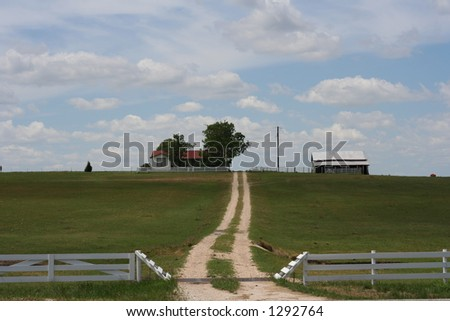 A farm on a hill in Central Texas. White wooden fence around. Curvy unpaved road leads to the house. - stock photo