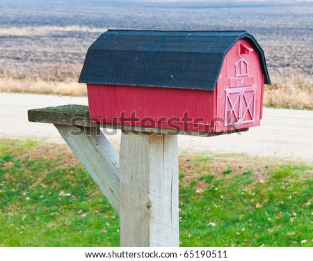 A farm shaped mailbox on a dirt/gravel background - stock photo