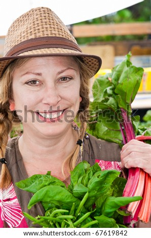 A farm woman in a hat posing for a photograph - stock photo