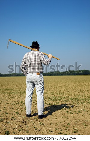 A farmer checks the small plants in a field in agriculture. - stock photo