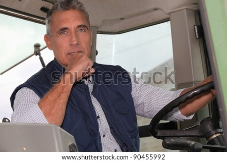 a farmer in a tractor cabin is driving - stock photo