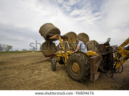A farmer moving round hay bales on the family farm.  It's a one man operation and always lots of work to do. - stock photo