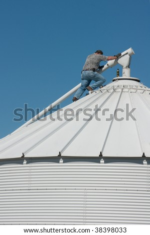 a farmer on top of a grain bin