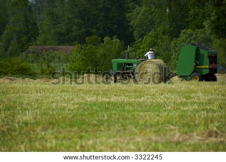 A farmer plows his fields using a green tractor